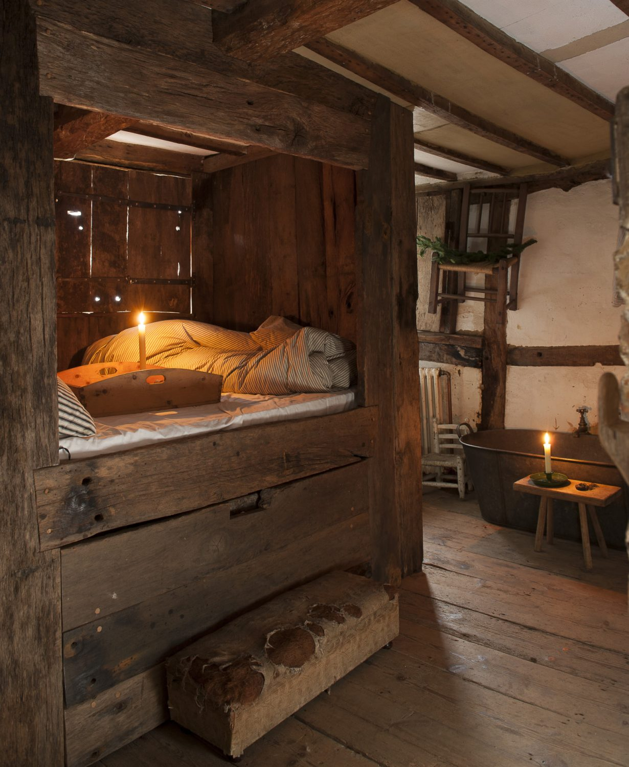 The main bedroom, with its Tudor 'en suite' is home to a raised bed enclosed by wood panelling and shutters