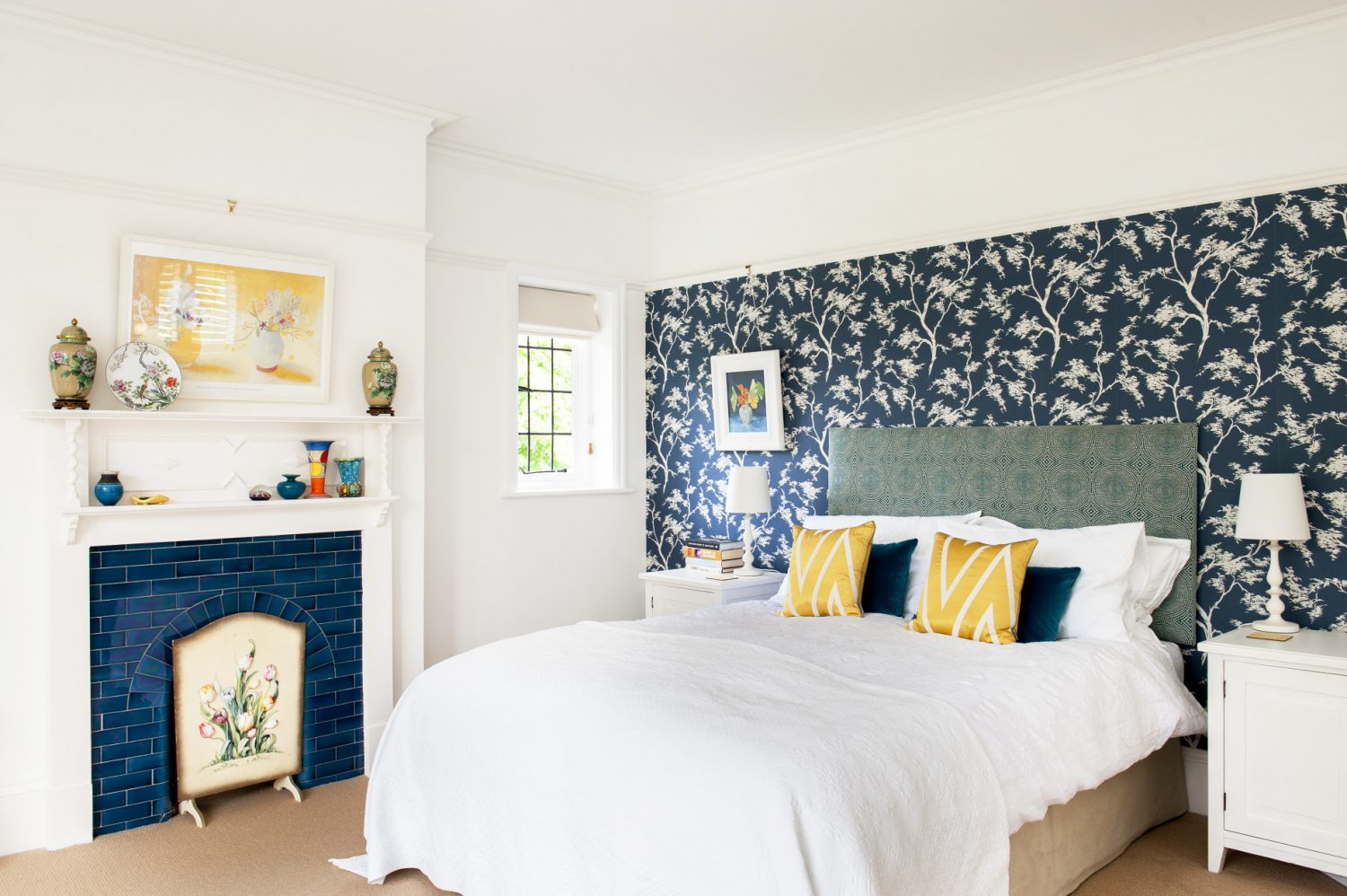 With off white walls on three sides and a lovely shade of indigo patterned wallpaper on the fourth – which picks up the blue tiles of the fireplace – it is a very calm room
