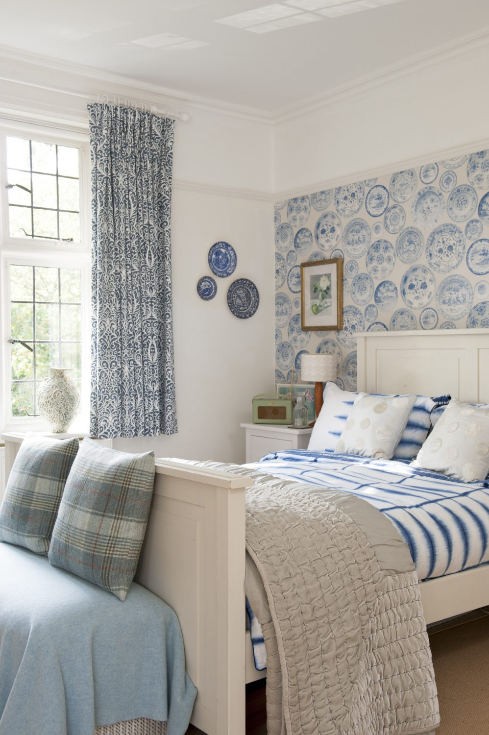 At the end of the landing is a really pretty guest room which features an Andrew Martin willow pattern plate design wallpaper, colours from which have been picked up in curtains, throws and cushions