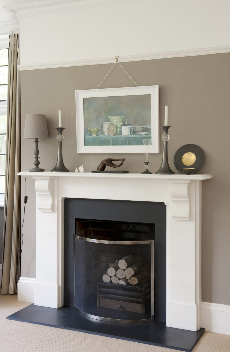 The fireplace is surrounded by neutral, restful tones