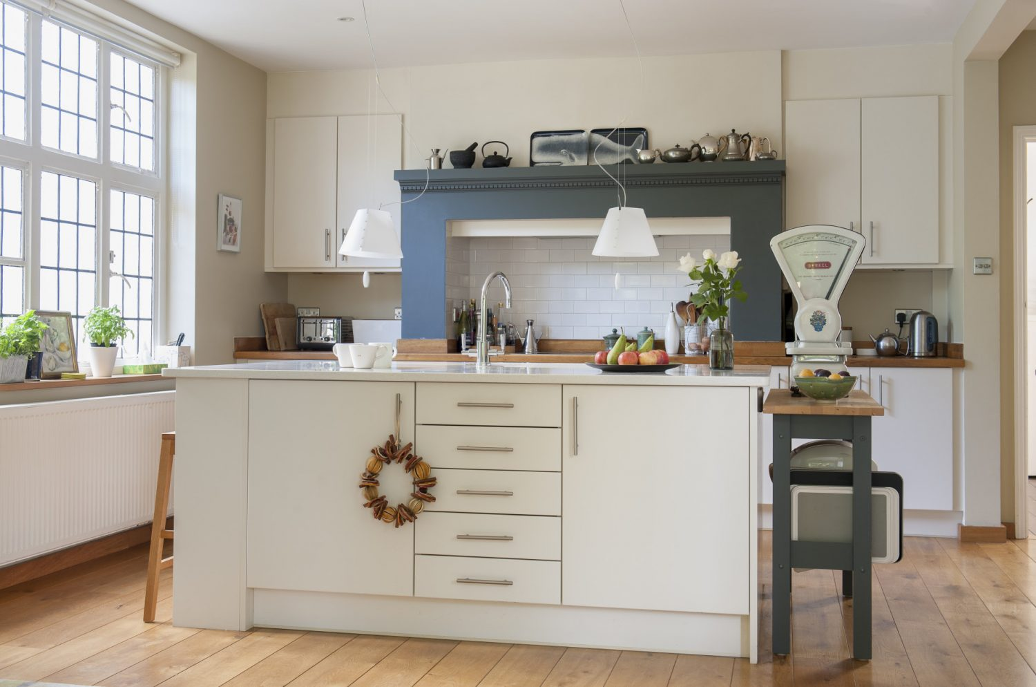 The kitchen is dominated by a free-standing unit painted in Farrow & Ball Slipper White. Featuring big and bold is a magnificent set of scales