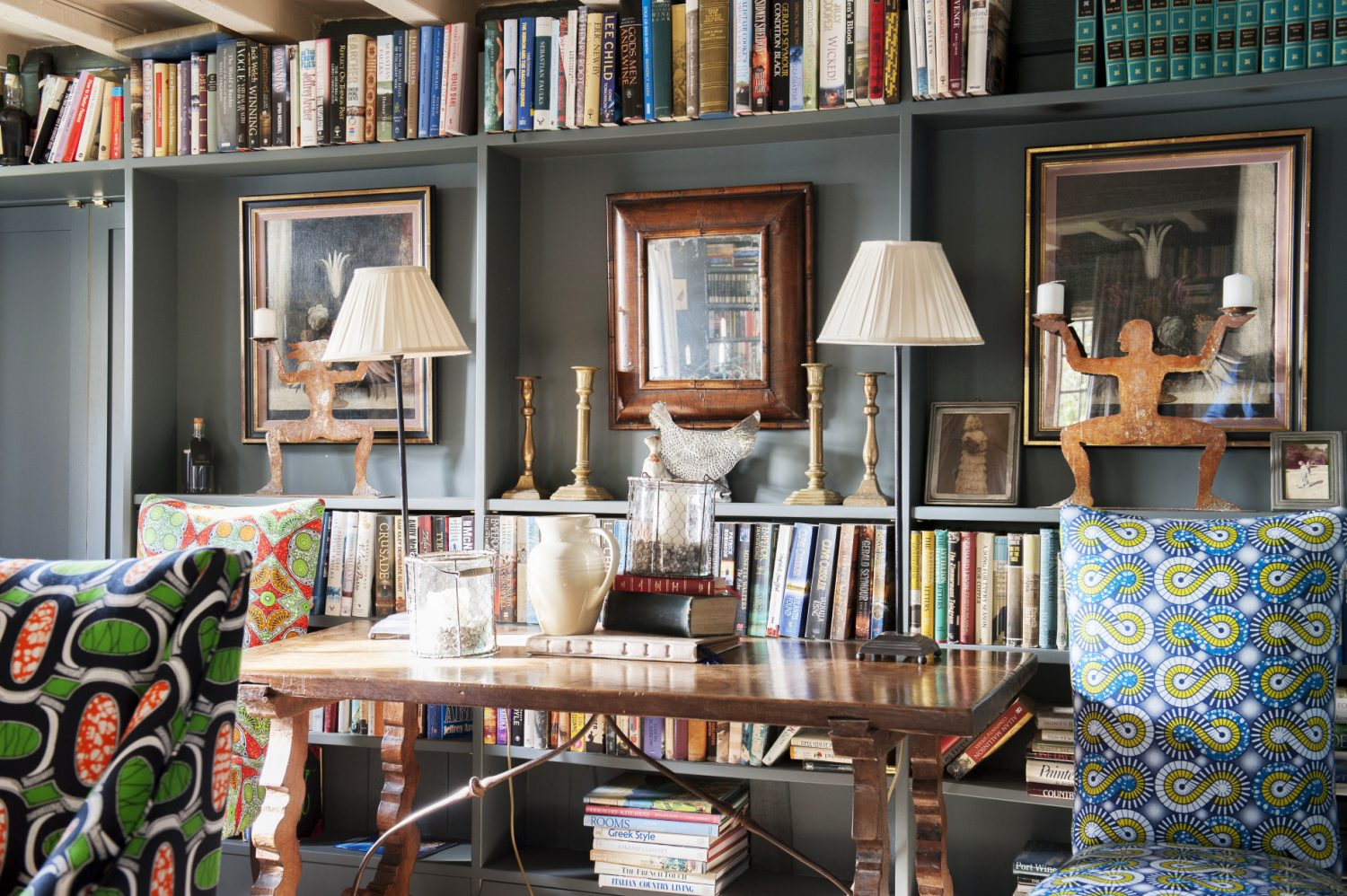 In the dining room the walls and bookcases are painted a dark grey – though Ally has managed to keep the room from feeling dark and oppressive by painting the ceiling and its beams off-white