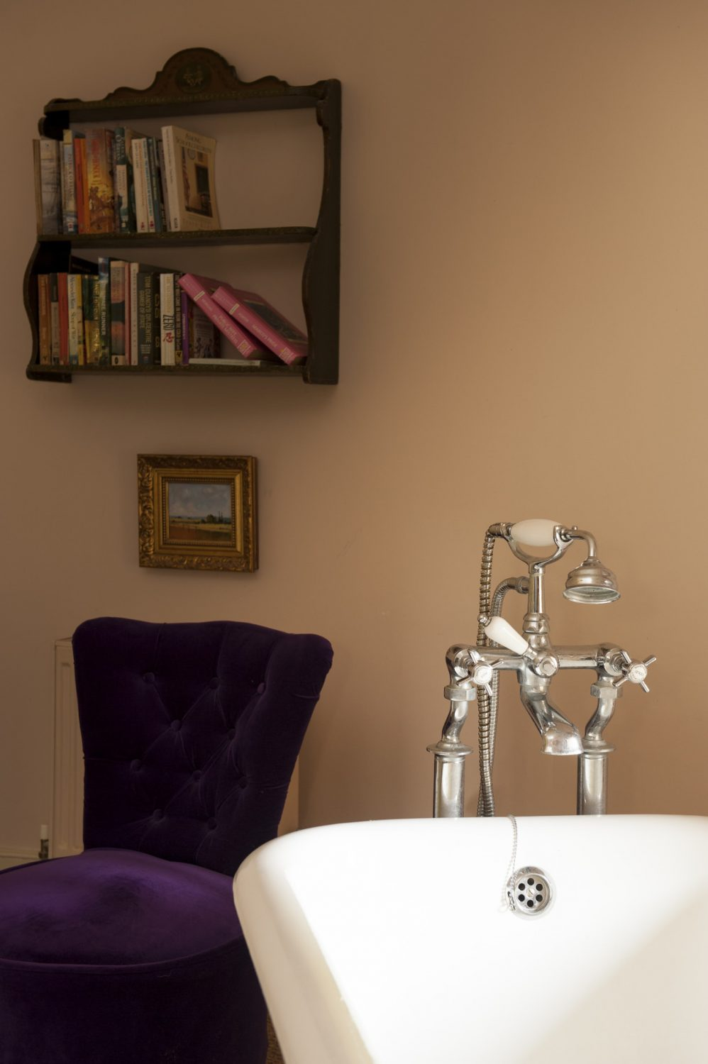 A purple velvet upholstered chair sits by the bath