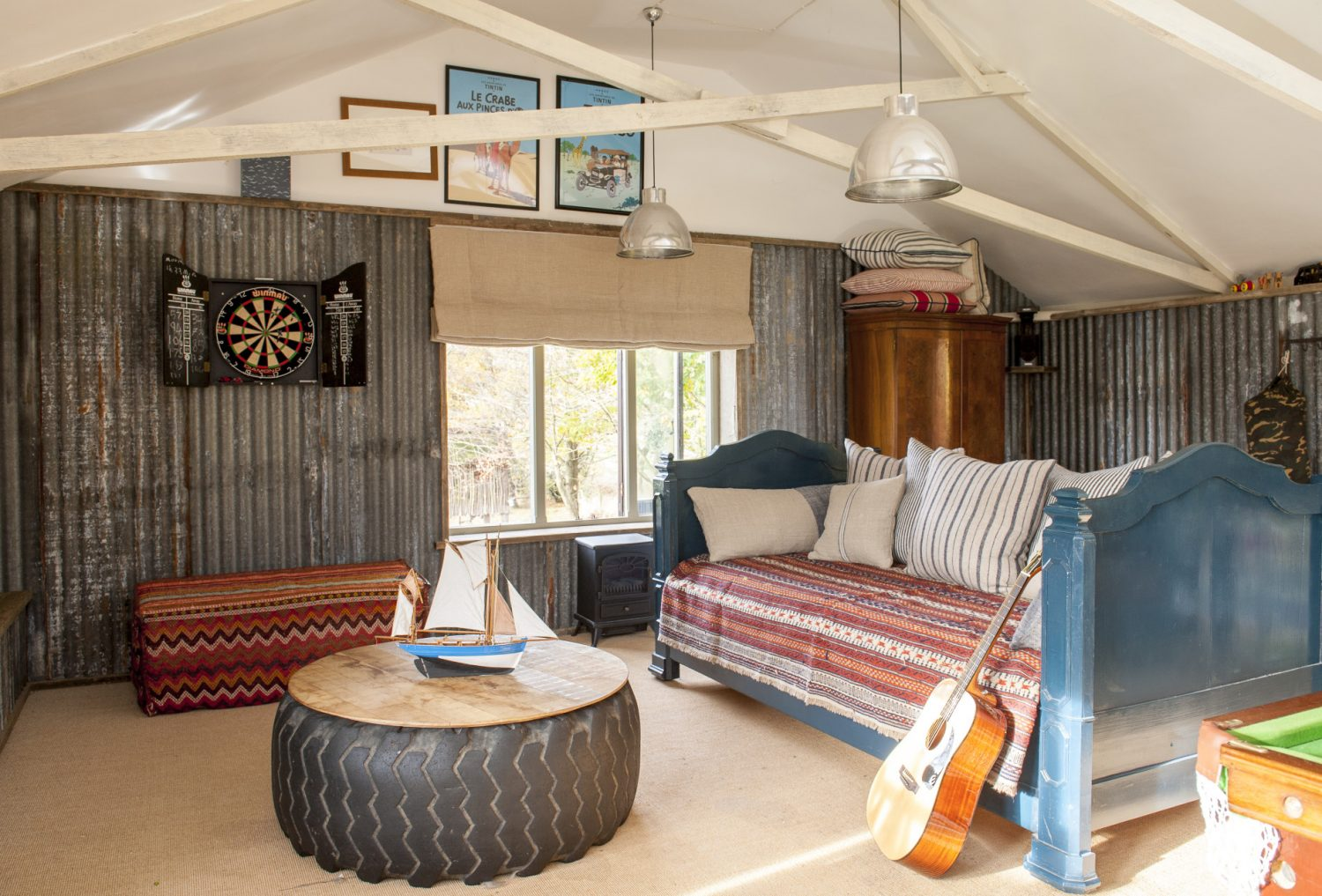 The den's walls are covered in corrugated iron, which Ally retrieved from various local farmyards, or reclaimed scaffold boards, and a tractor tyre has been topped with planks and turned into a table