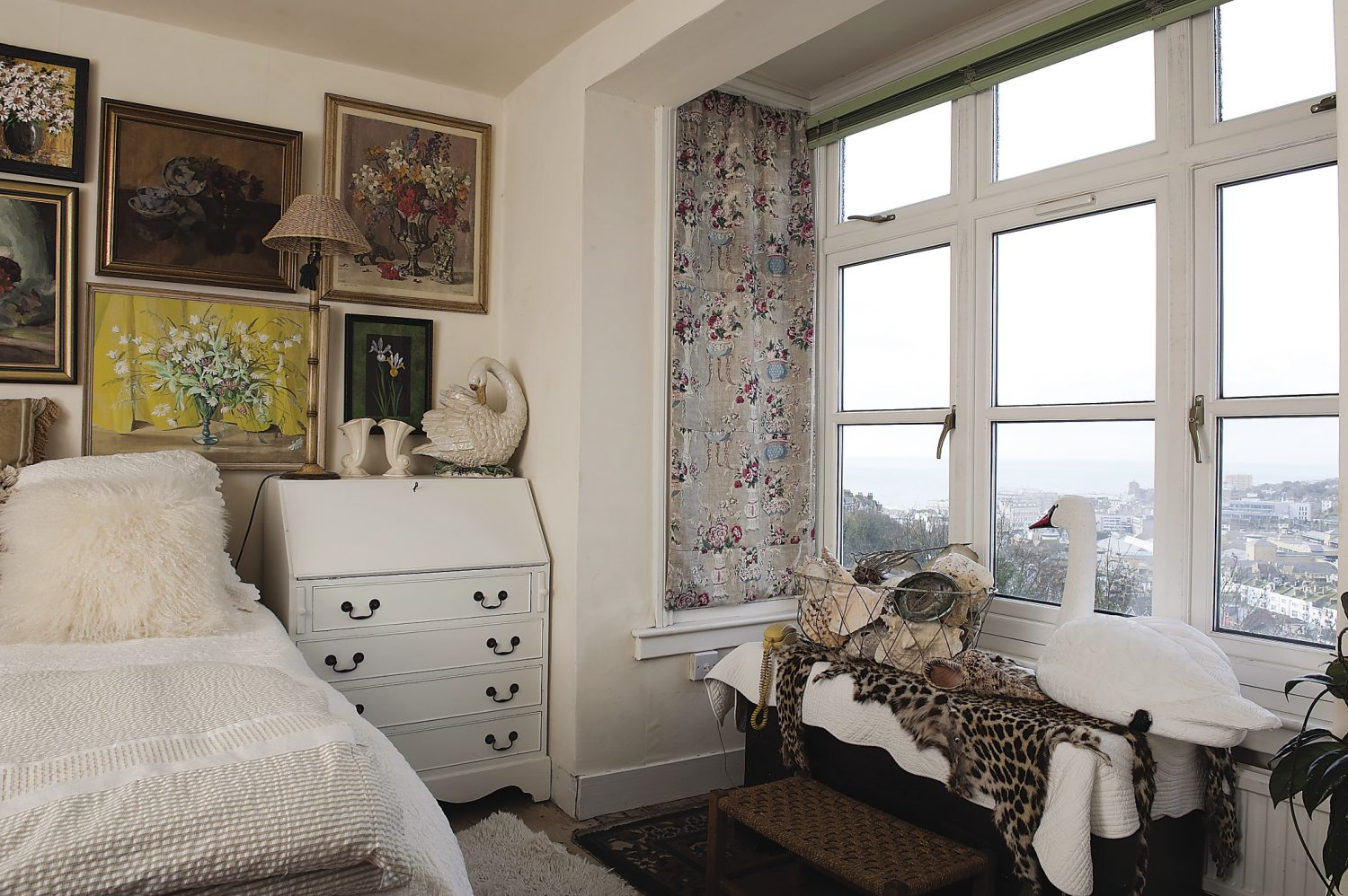 Helen's bedroom has great views of the sea and town. Helen's bed is dressed with a hand-made ivory quilt and masses of cushions, some of which have been sewn from the same linen that Helen had used to make window panels