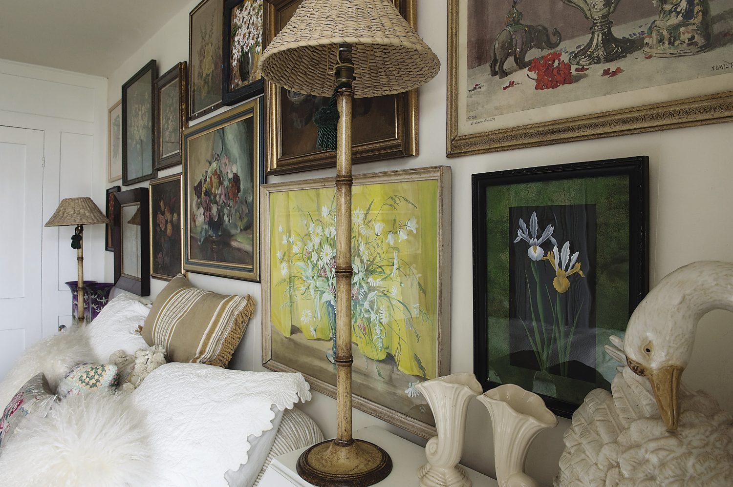 The wall above the bed is a joyful collection of oil and watercolour paintings of flowers