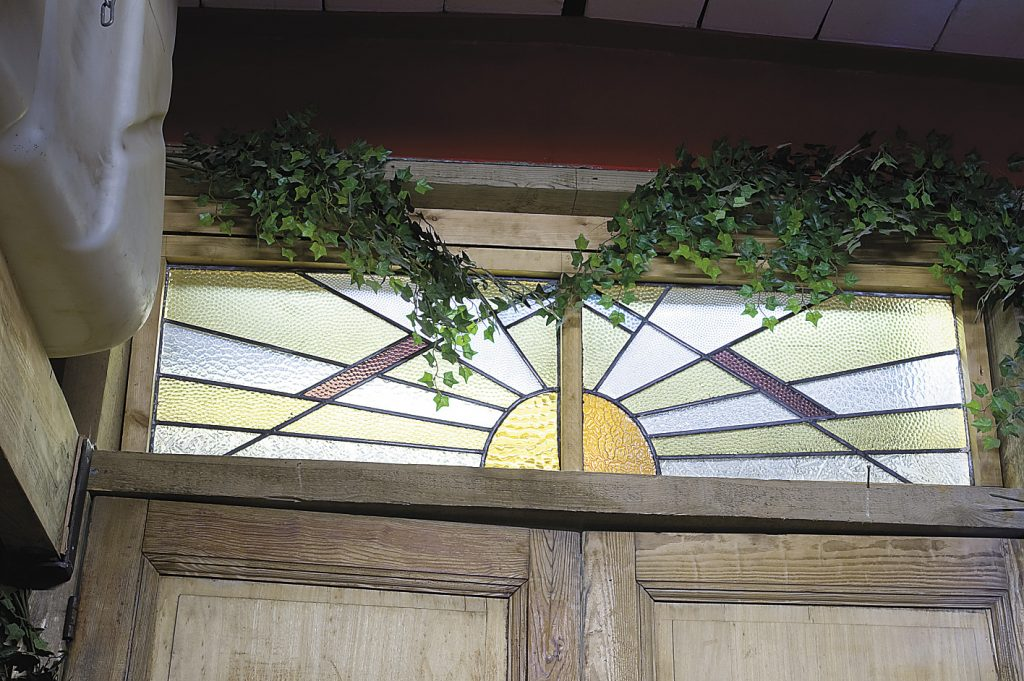the dividing wall below decks in the summer quarters is made up from stained glass windows salvaged from a pub
