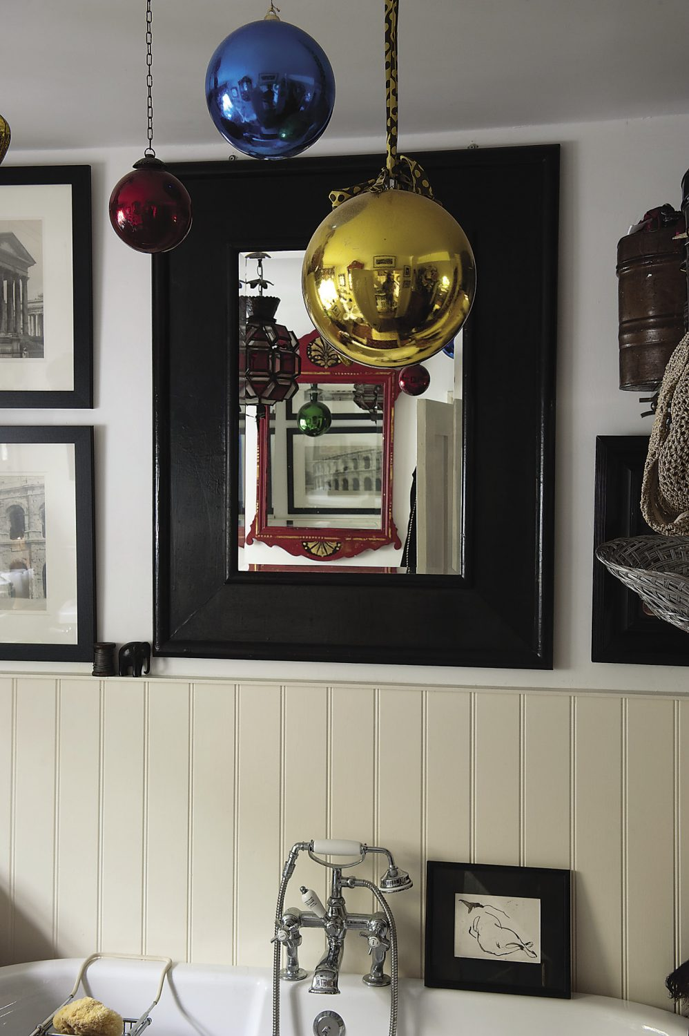 Helen has cleverly hung eyecatchingly colourful baubles above the roll-top bath in the ground-floor bathroom to disguise the 'scar' across the paintwork caused by the removal of a strip light