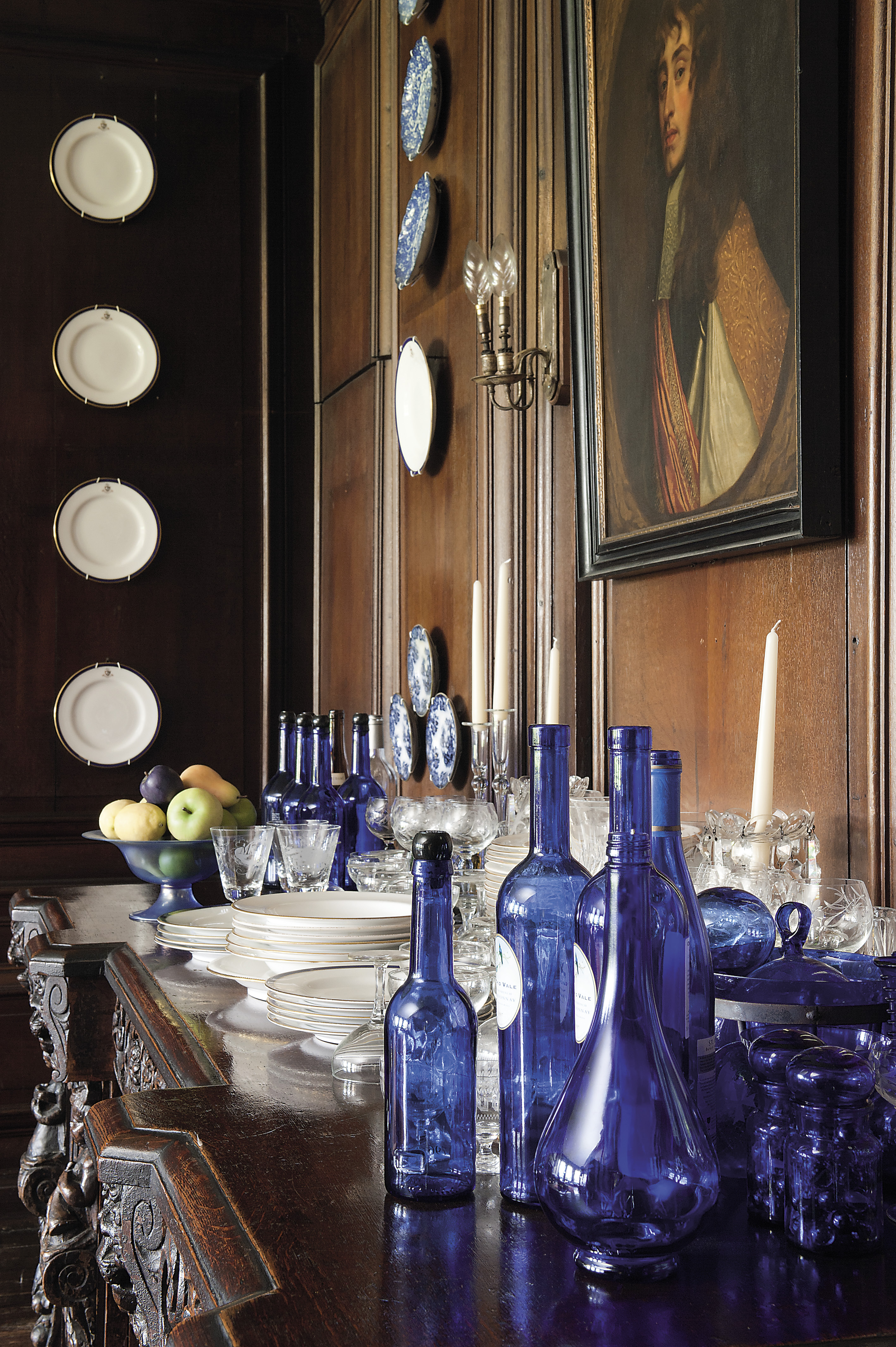 Beneath a portrait of James II when he was the Duke of York, a florid Victorian sideboard supports a white china dinner service and cobalt blue glass