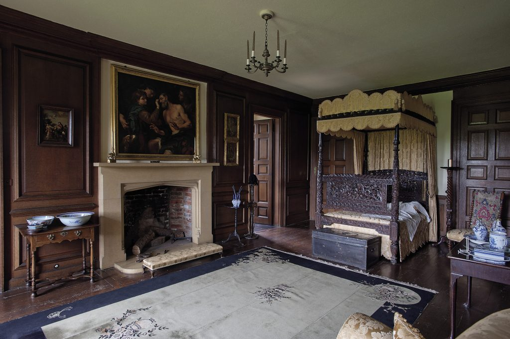 The State Bedroom of Queen Anne is entered through a door that leads off the State Drawing Room and features an intricately carved four-poster bed, at the base of which is a leather trunk studded with the Queen's cipher on the lid