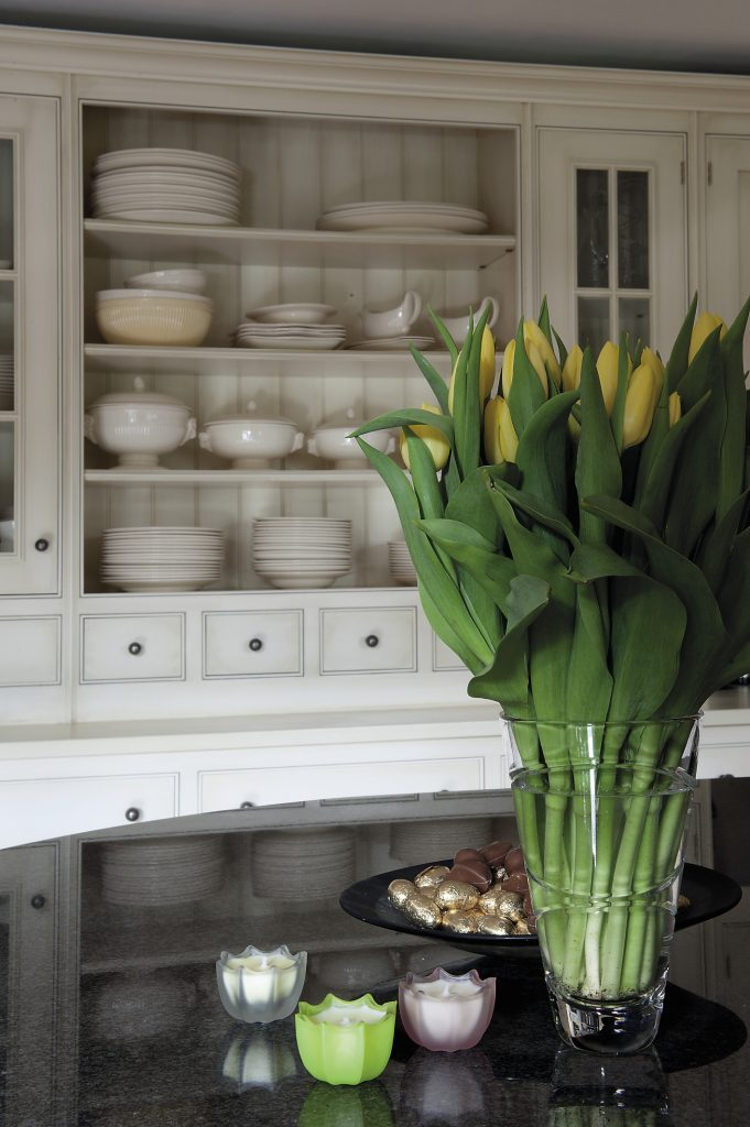 In the kitchen, glass-fronted cabinets house a huge collection of cream Wedgwood Queen's Ware