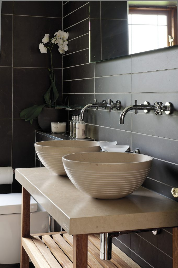 """White phalaenopsis orchids are a feature in almost every room of the house (pictured here in the family bathroom) """"I get all my flowers from Flower & Glory in Sevenoaks. I just take in the bowls and planters and Deborah fills them with really beautiful plants that she sources from Covent Garden flower market,"""" Candy says"""