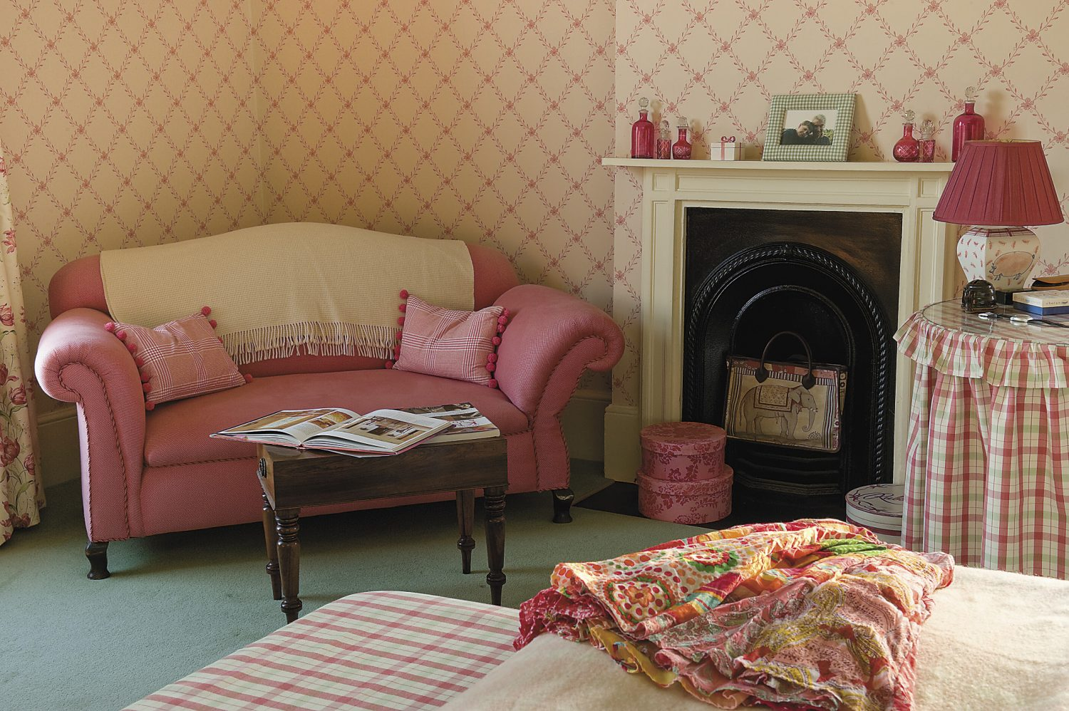 the ruby coloured sofa by the fire in the main bedroom provides the perfect place to relax