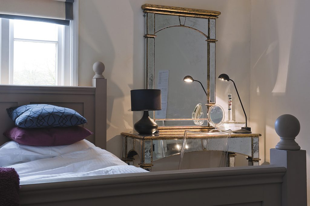 this mirrored console table and old looking glass are put together to create a dressing table in John and Sandy's daughter's room