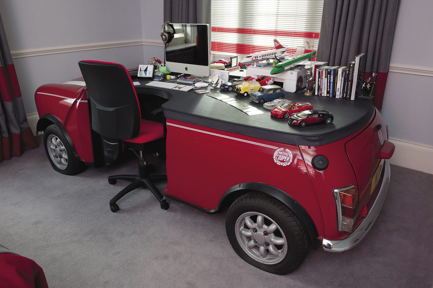 Theodora's teenage son's bedroom is a homage to The Italian Job. A full size Mini Cooper has been converted into a desk and the curtains feature the Mini logo as the pelmet motif