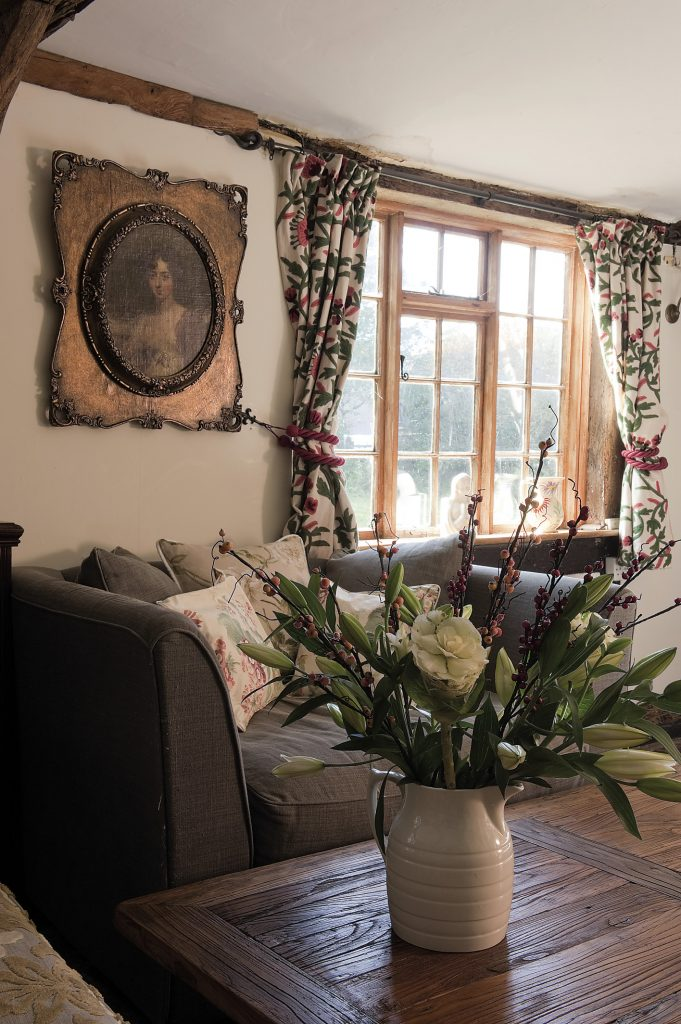 The windows are framed by curtains made from vivid red and green crewelwork linen twill from Bell House Fabrics in Cranbrook.