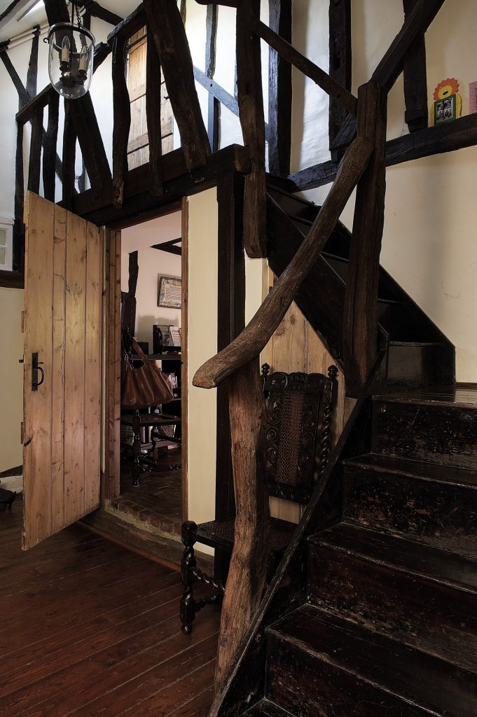"""The minstrel's gallery. """"This part of the house was an extension made in the 18th century. The main bit dates from the 15th century, I think, and you can still see the 'external' timbers. There's so much wood here that the whole house creaks like a ship on the high seas."""" Tucked under the stairs, a small door leads into Louise's office"""