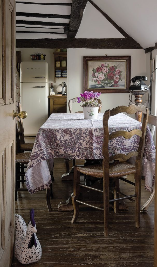 A wooden bench from an old ocean liner serves one side of the kitchen table, while delicately carved oak chairs, bought from the late lamented antiques shop in Sissinghurst, populate the remaining three sides