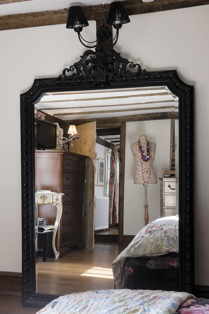 The master bedroom. An enormous mirror with an Empire style black frame has been propped up underneath a black wall sconce with finely taut 'string' shades A spriggy flower print covers the tailor's mannequin that displays a collection of vintage and African beads that Louise collected on her travels