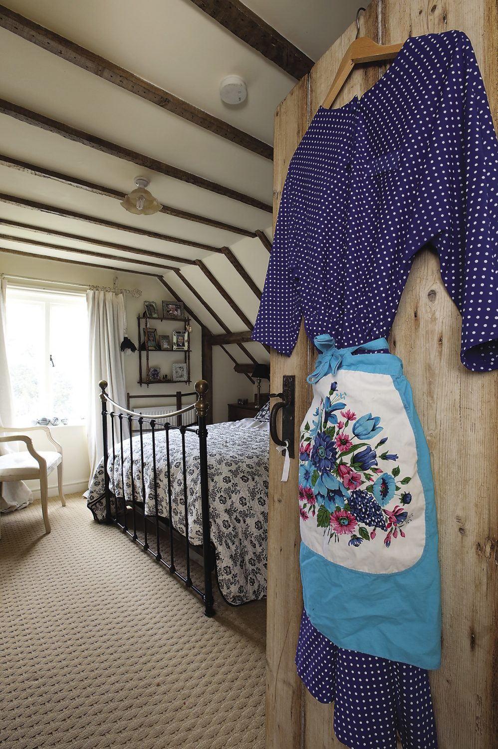 "The master bedroom. On the door hangs a cornflower blue and white spotty dress and 1950s floral apron. ""Pippa and I dress up for Happy Hampers,"" laughs Stella. ""You have to go a bit over the top though, because if you do it half-heartedly people don't get that it's vintage, they just think you dress a bit weirdly!"