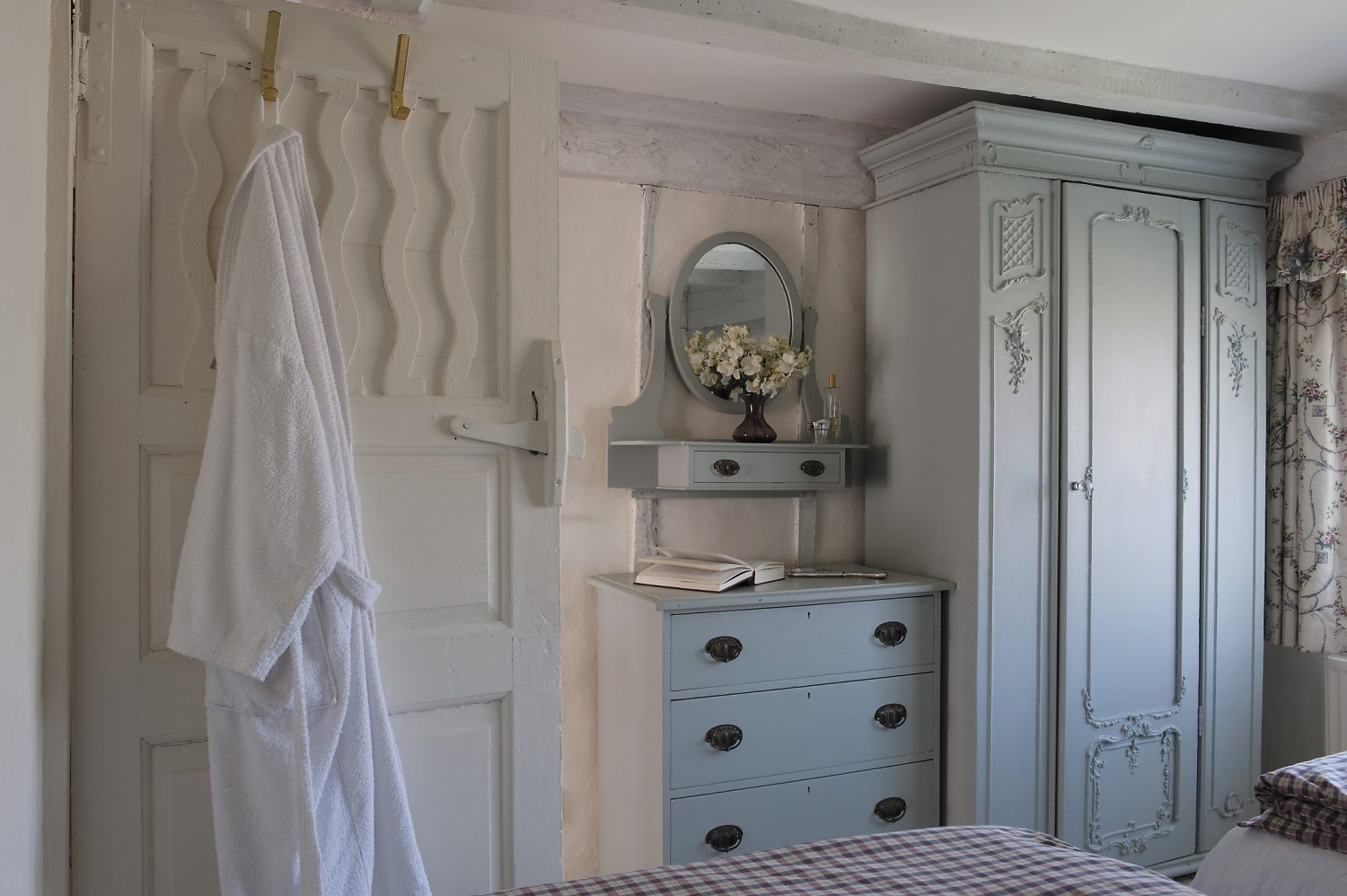 The guest bedroom is furnished with more of Dora's furniture – a prettily carved wardrobe and chest of drawers