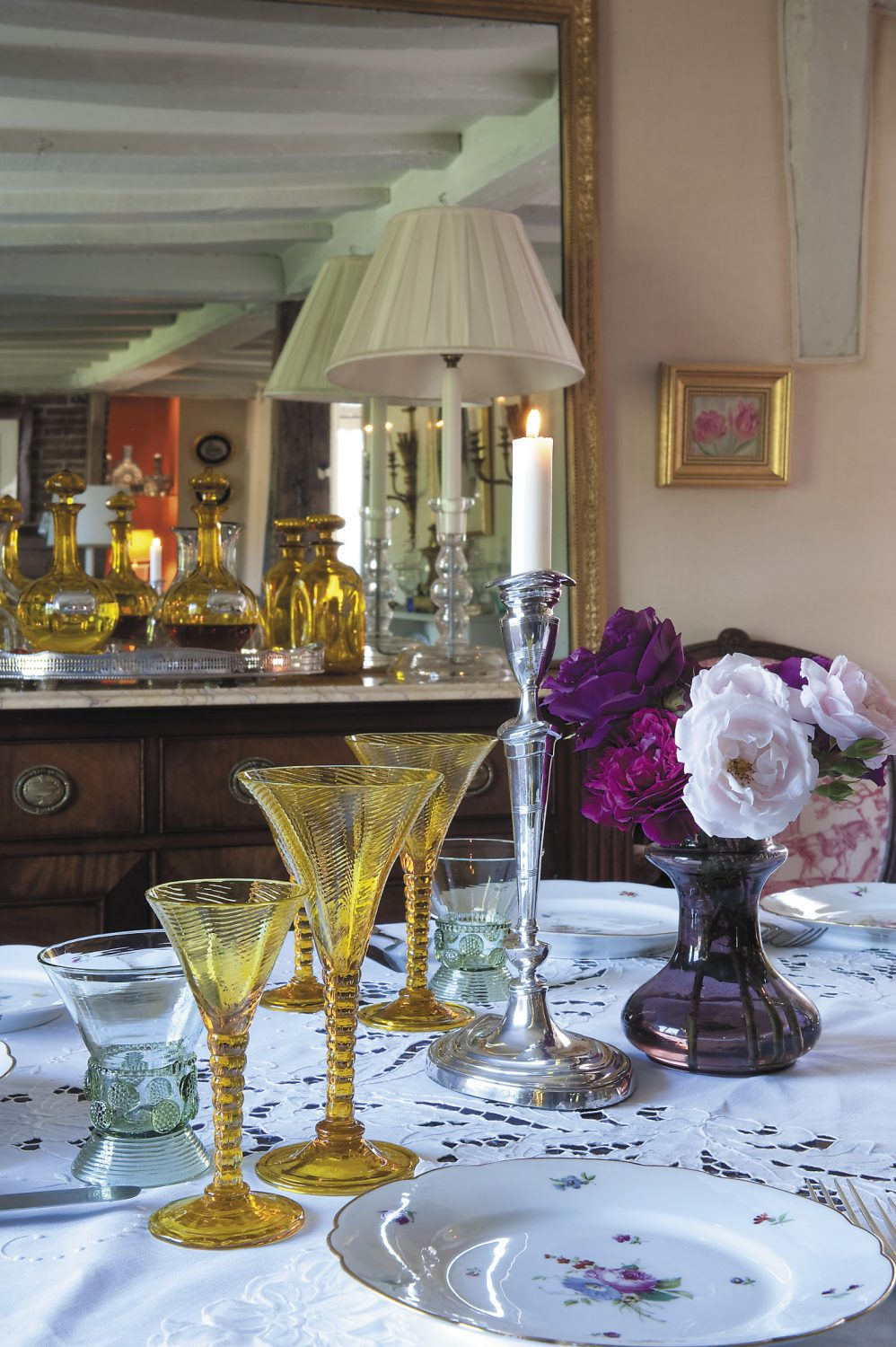 In the dining room an oval table is set with Bohemian amber glass