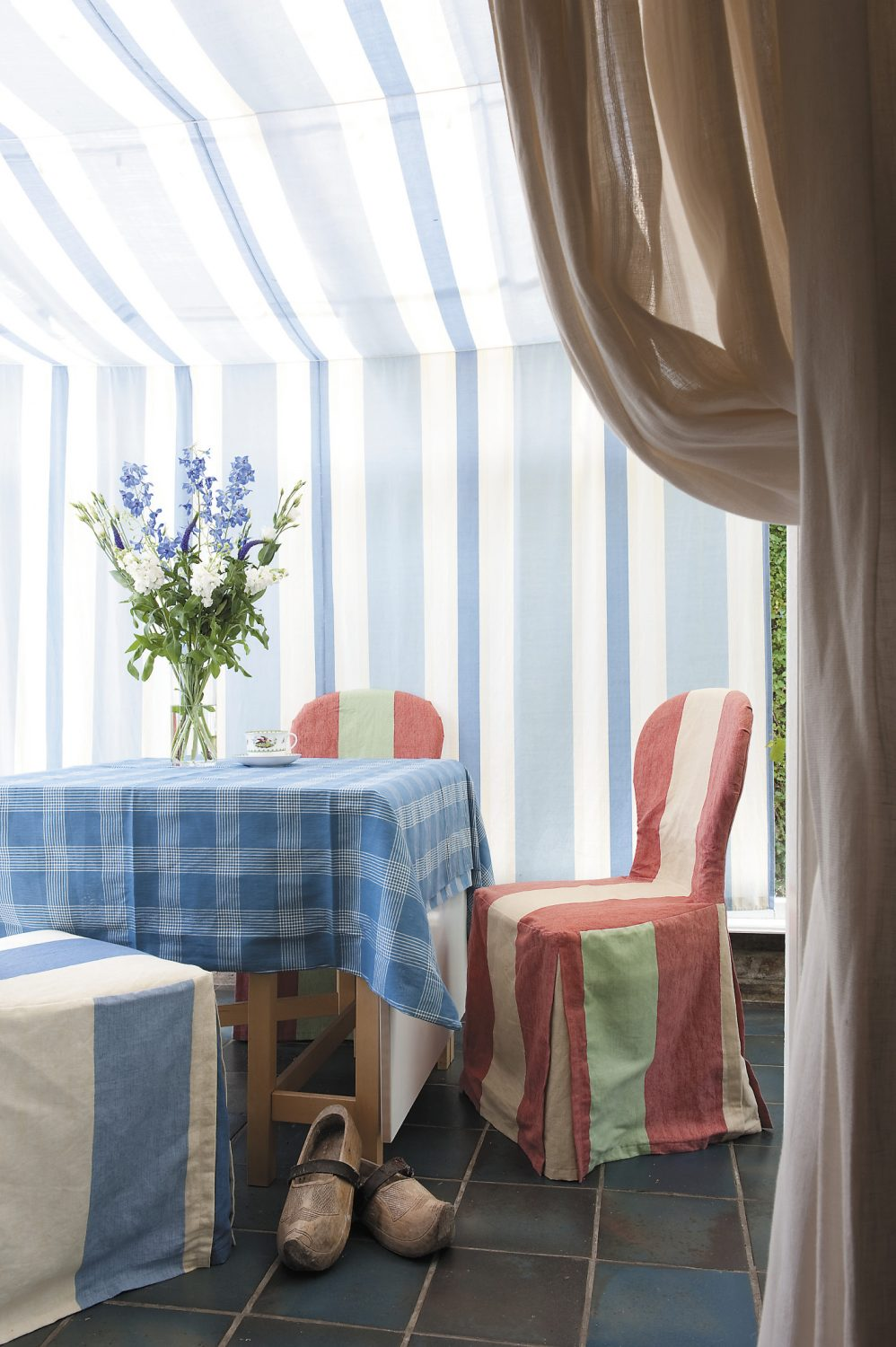 Just off the kitchen one finds a conservatory that has been tented with blue and white striped Jane Churchill fabric