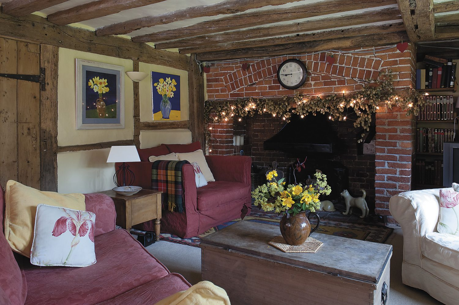 the inglenook is very much the centre of the home and is used in winter. On the wall, left, are Christine and Barry's paintings of daffodils