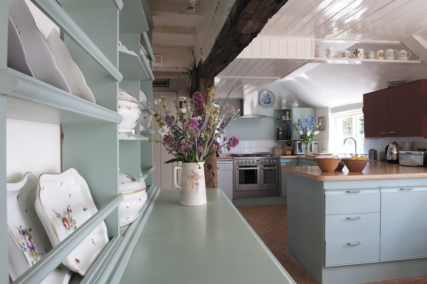 In the kitchen, a painted dresser and units display flowers from the garden