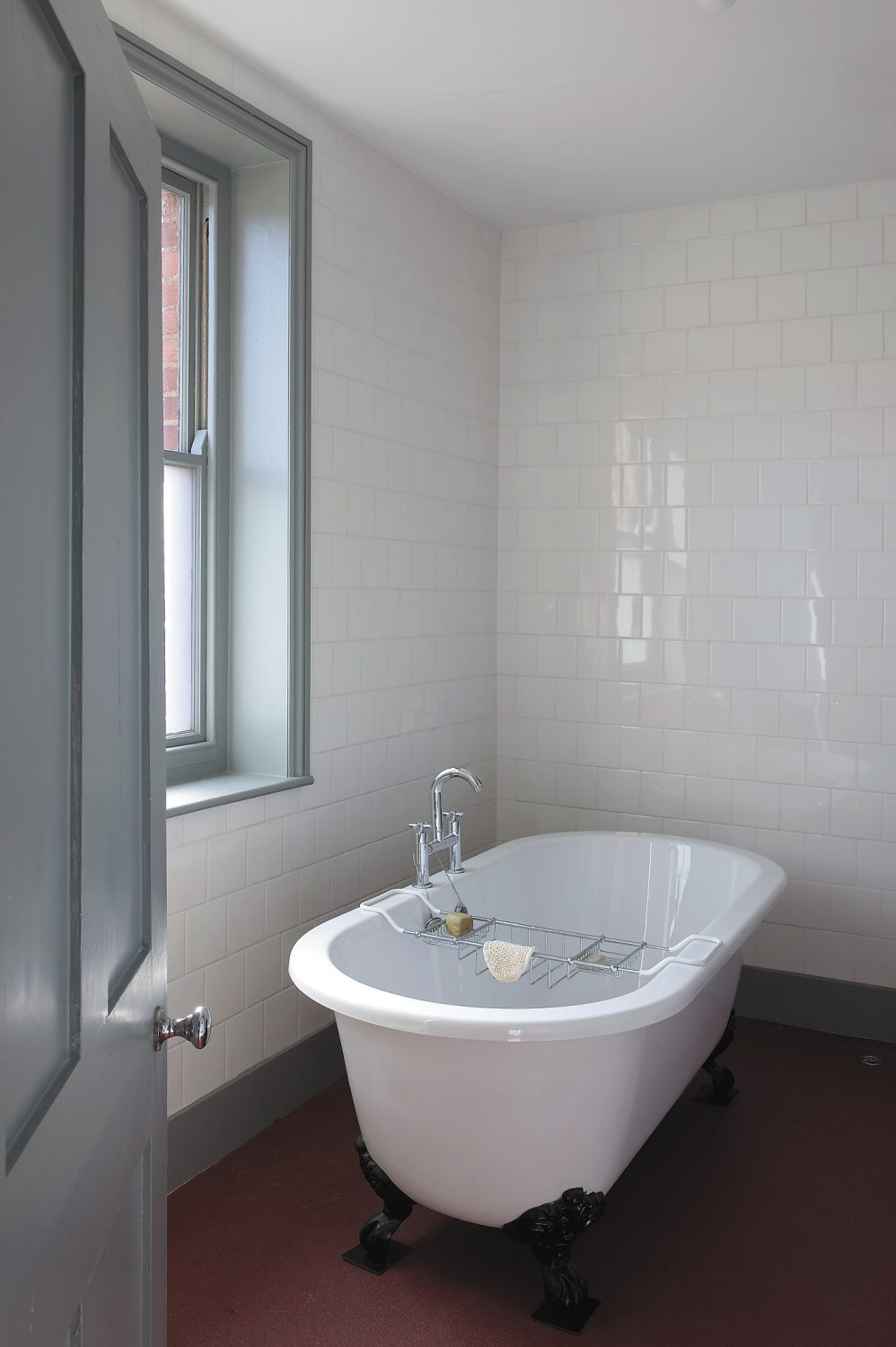the white tiled bathroom has a free-standing bath and walk-in shower