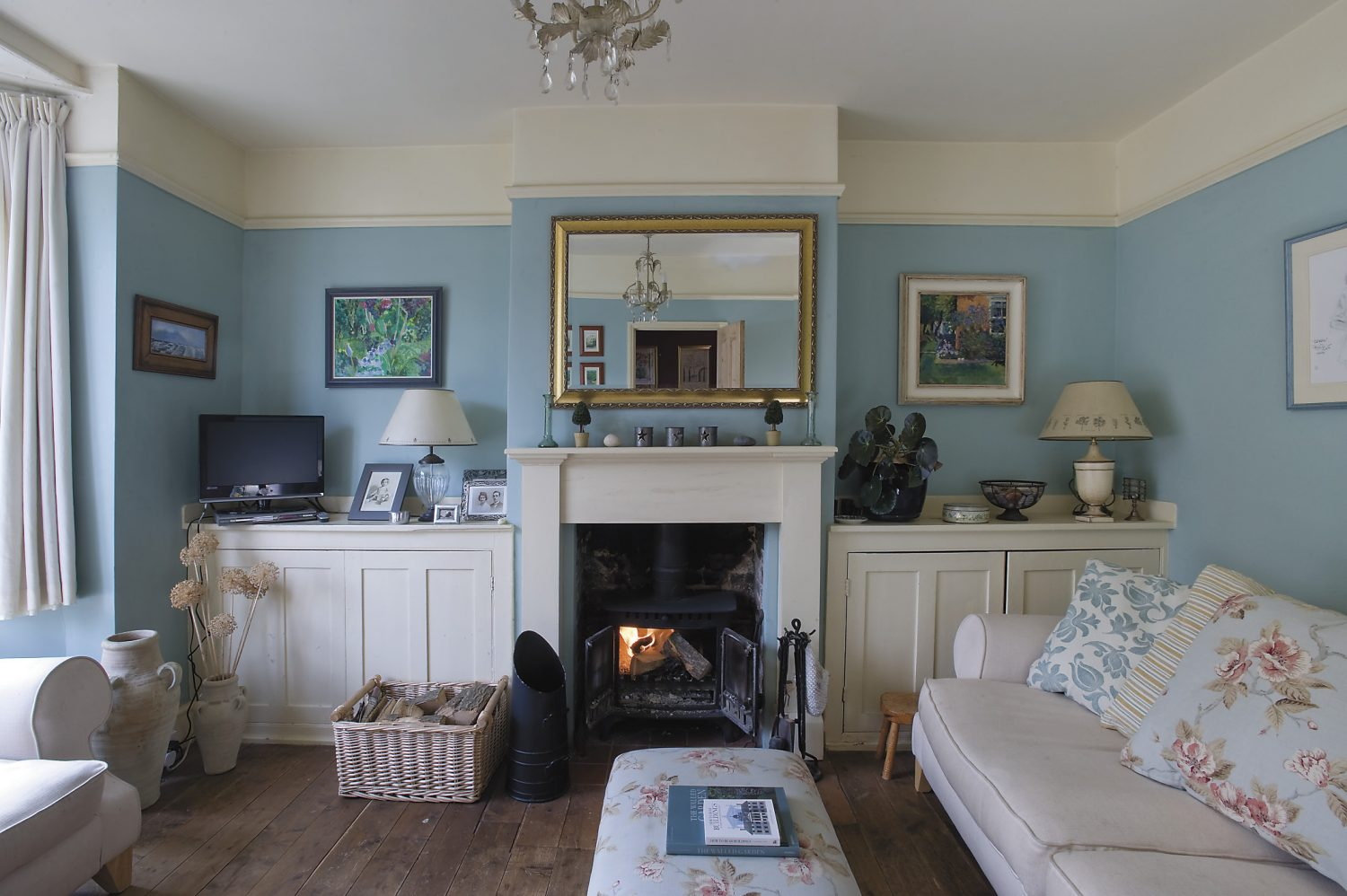 the duck-egg blue drawing room, at the front of the house, was added on in the Georgian period. The painting on the right-hand side of the fireplace is by Frittenden artist Anne-Catherine Phillips