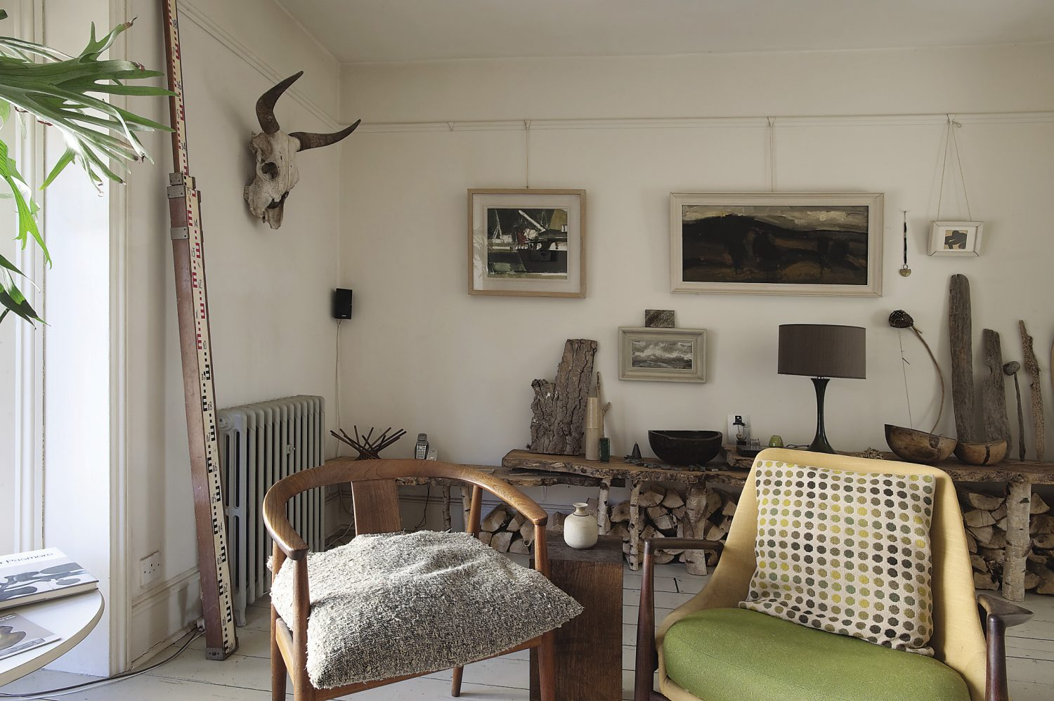 The sitting room. Offcuts from an elm tree have been used to make a shelf on one wall, supported by legs made from silver birch logs.