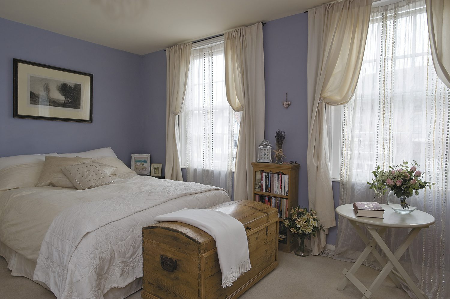 the main bedroom has lilac walls and ivory curtains. The lithograph above the bed is French