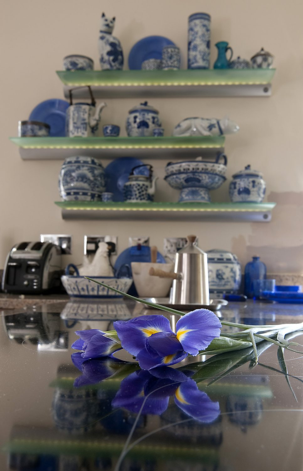 """In the kitchen, shelves of blue and white Thai china dominate one wall. """"We won quite a few of these pieces at bridge games in Thailand, and as we had so many of them, they rather dictated the colour scheme in this room,"""" says Mike"""