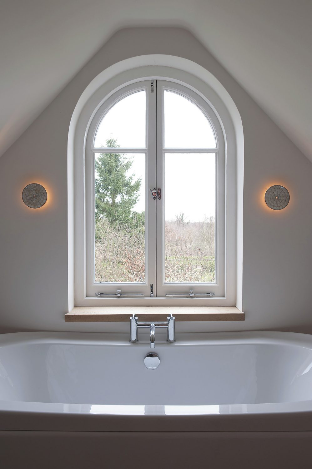 the arched window in Sally's bathroom looks out over farmland