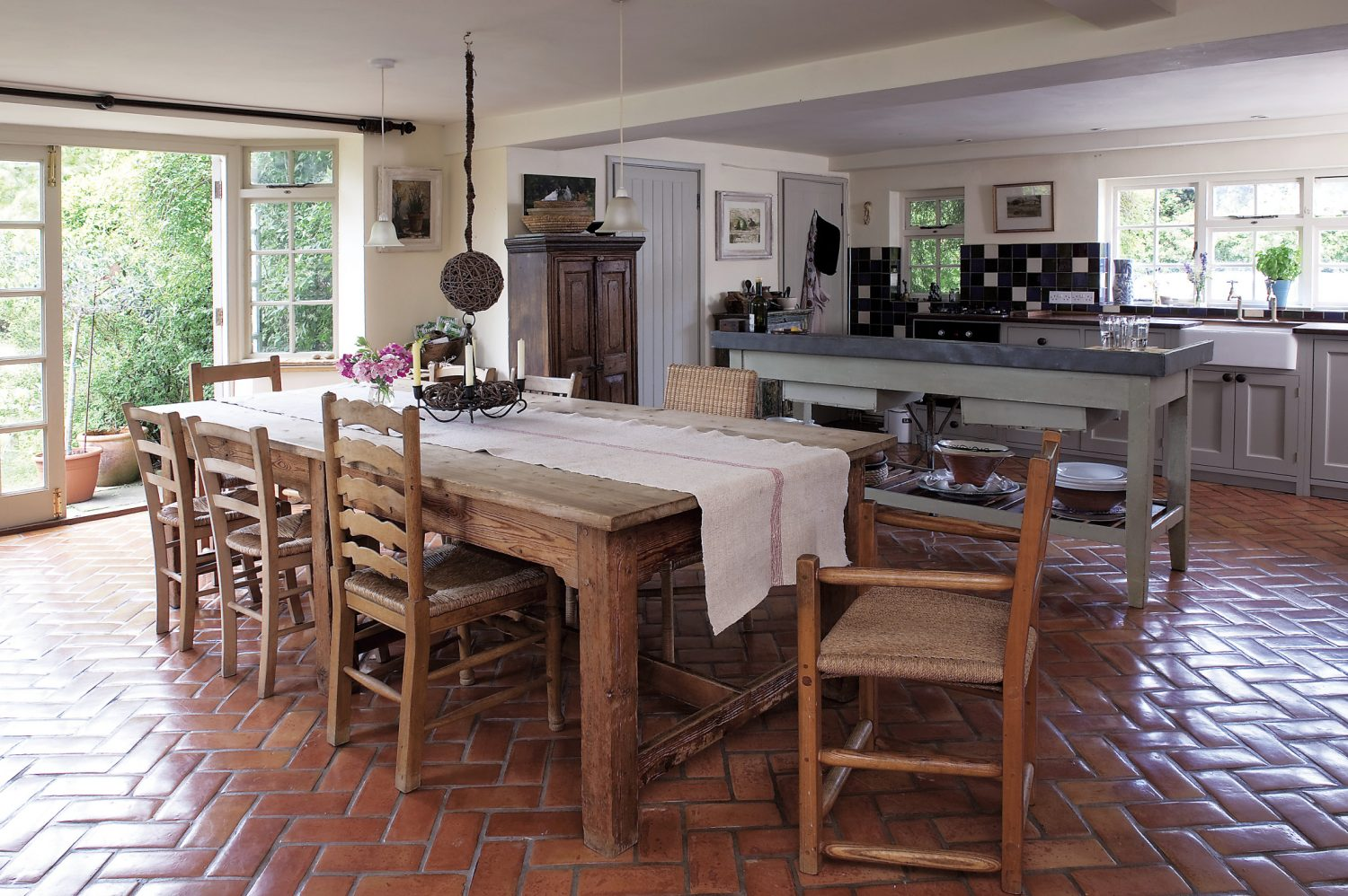 In the kitchen old French zinc-topped garden potting table makes superb six-foot preparation table and distressed French cupboard stands nearby.