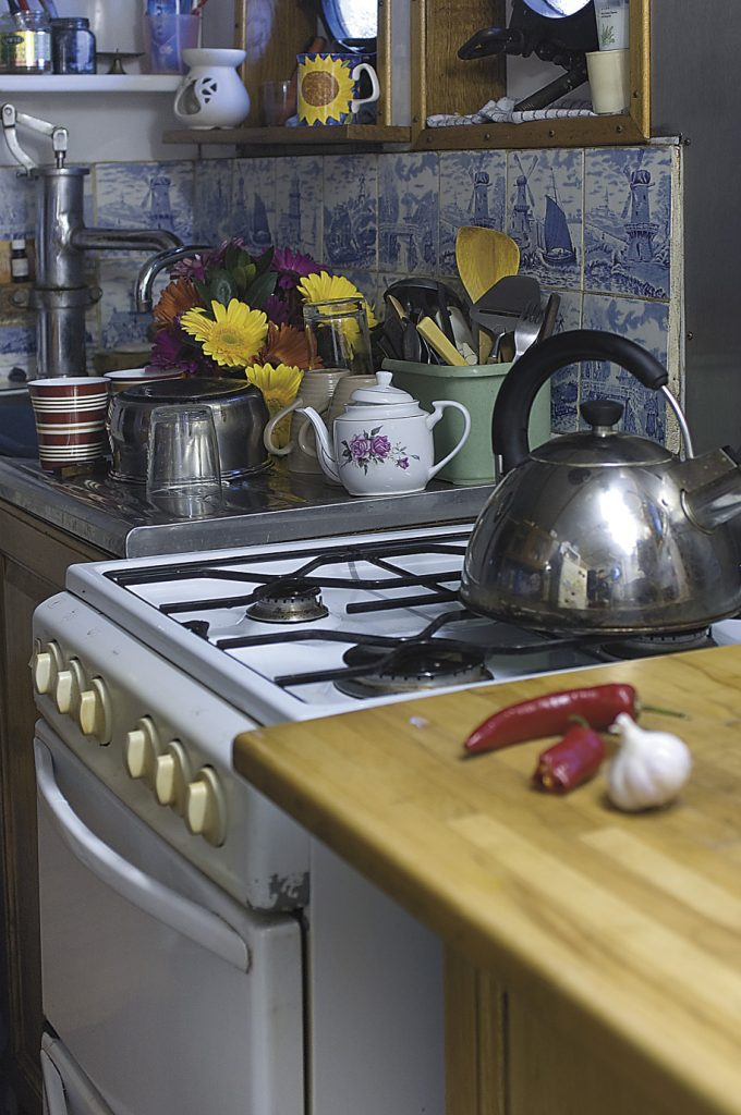 the tiny 'galley' kitchen is decorated with reclaimed blue and white tiles