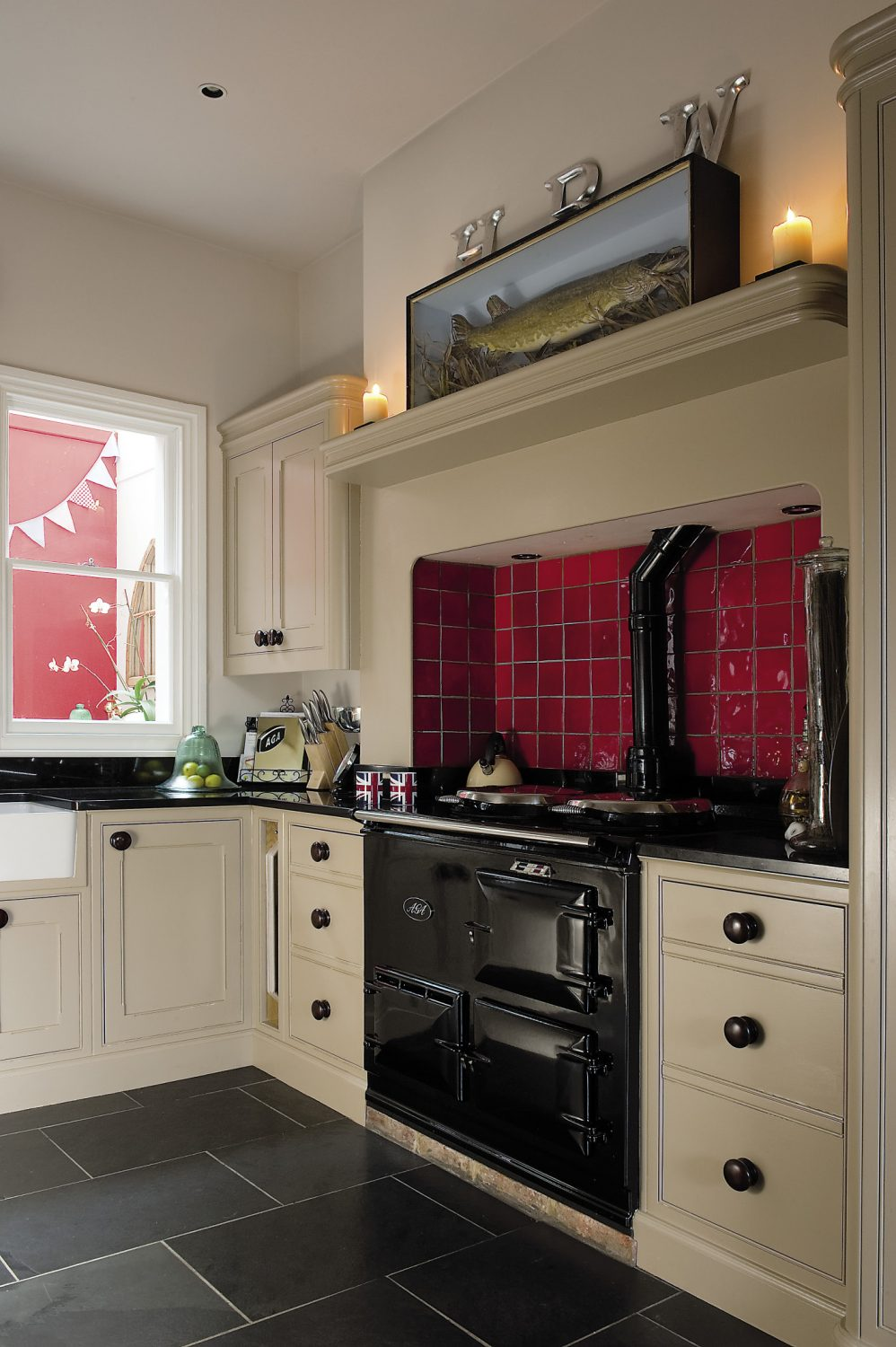 """A shiny black Aga warms the room and behind it, the alcove has been covered with scarlet tiles. Sally loves to cook so it's also a very practical and efficient space: """"The Aga was non-negotiable,"""" she says flatly. """"I've always cooked with one."""""""