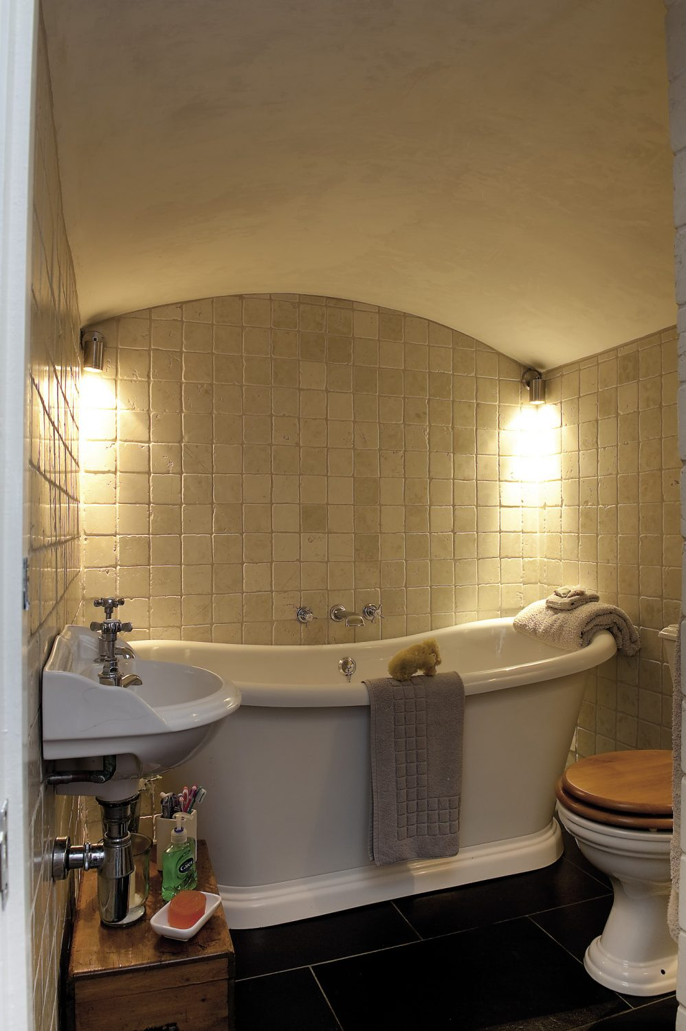 Housed in the former coal chute, the curved ceiling of the bathroom has been retained, so that with the huge freestanding bath and the limestone mosaic tiles, the room has more than a hint of the Roman baths about it.