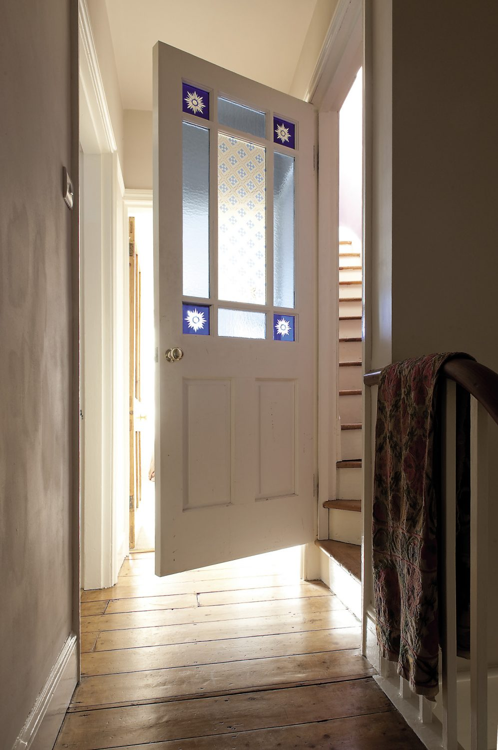 A wooden door with stained glass inserts leads to Bobby's room on the top floor