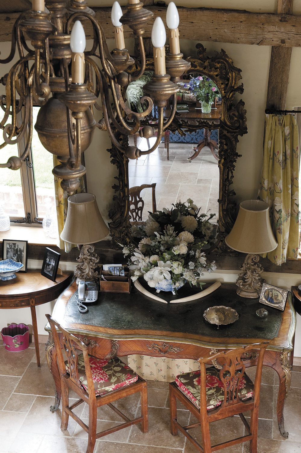 a large ornate gilt looking glass hangs above a Louis Seize desk that once stood in Macroom Castle in County Cork