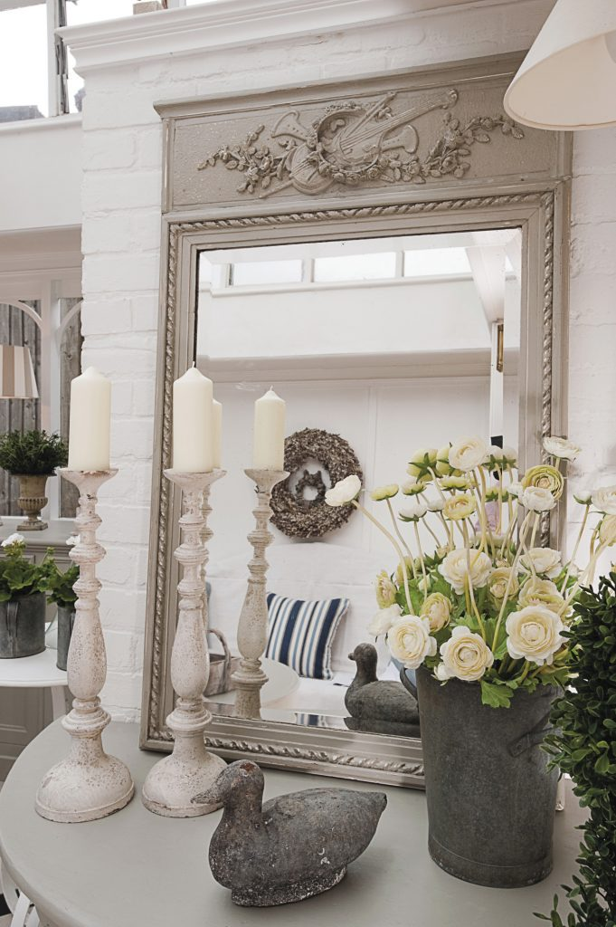 a pretty mirror and a pair of candlesticks, as well as more faux flowers in the form of ranunculus and tall white delphiniums, enhance the conservatory