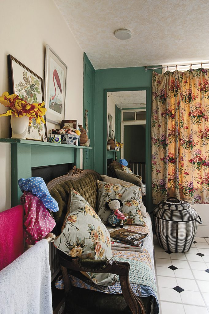 the bathroom sofa is covered with quilted throws and floral cushions