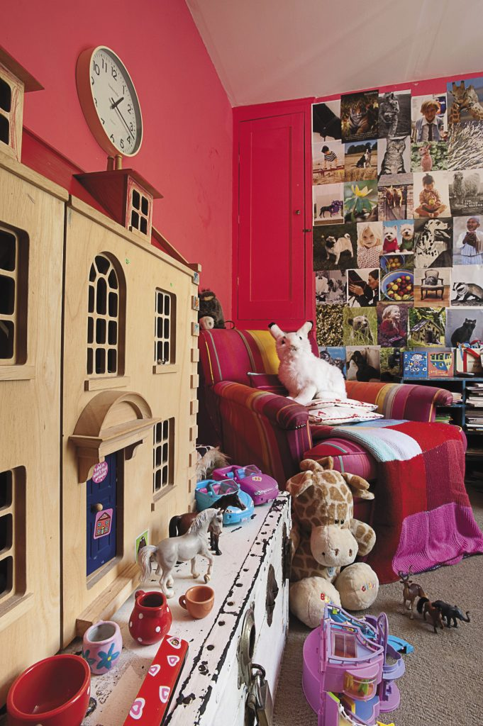 one of the pink playroom walls is papered with favourite pictures