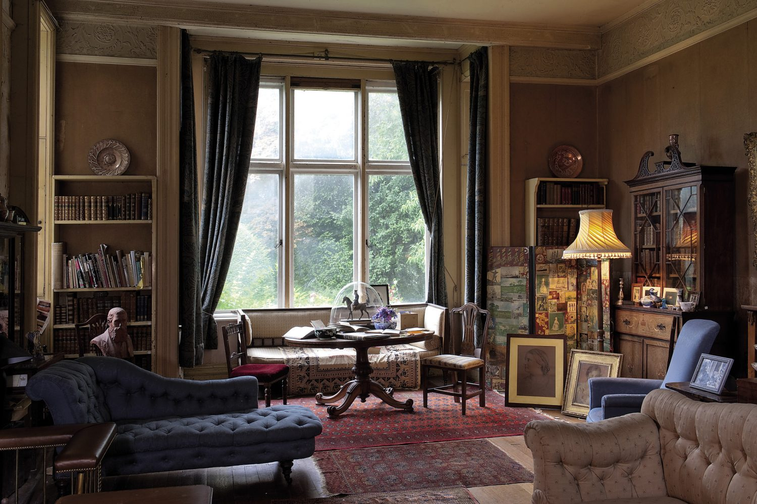 The drawing room: part of the most recent (Victorian) extension added by Milicent. It is a big room that features tall ceilings and has as air of austerity. The William Morris curtains suggest how grand this room might once have been