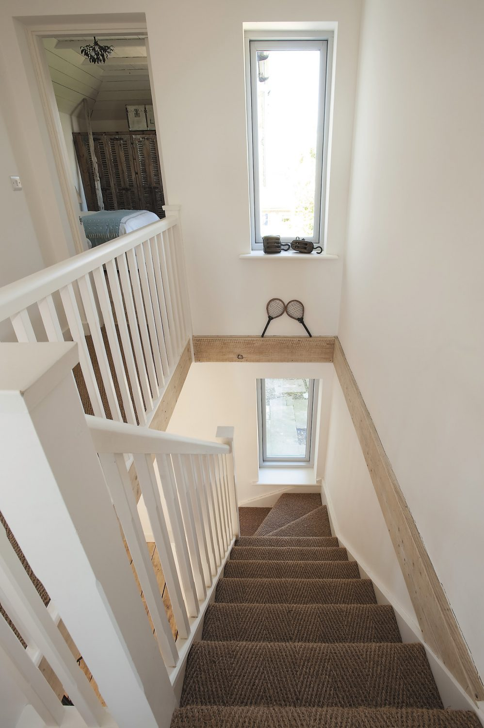 The staircase was repositioned to make the most of the light and available space; the hoists on the window ledge were probably used originally by local fishermen. The seagrass was sourced from Avalon Flooring