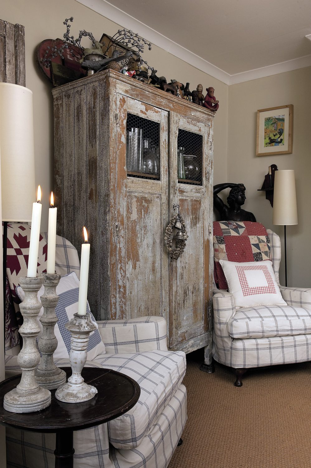 A large distressed grey French cupboard stands at the other end of the dining area, its long-lost original glass panels replaced very effectively by humble chicken wire