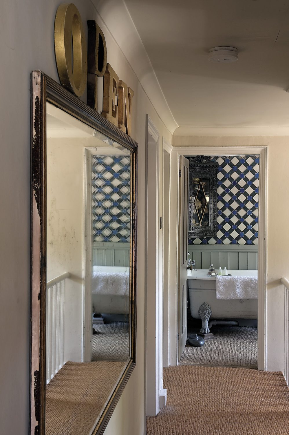 The view into the bathroom, past a huge gilt mirror
