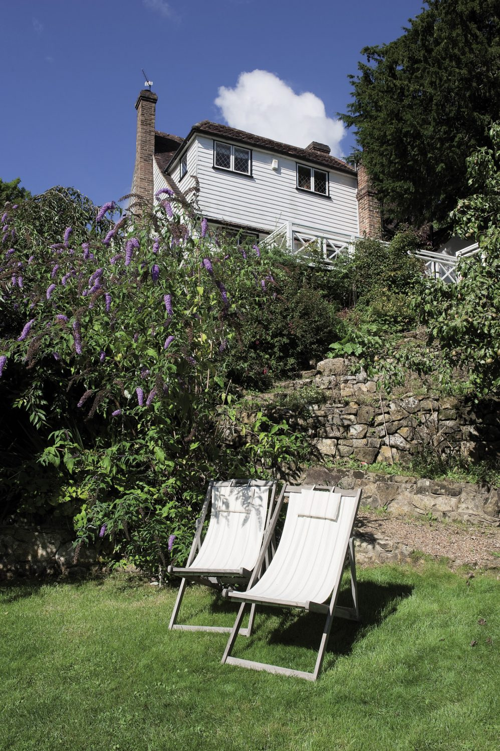 The summerhouse has been painted a pale Dior grey and beside it a pair of deckchairs ,newly covered with grey and white striped canvas, face the autumn sunshine