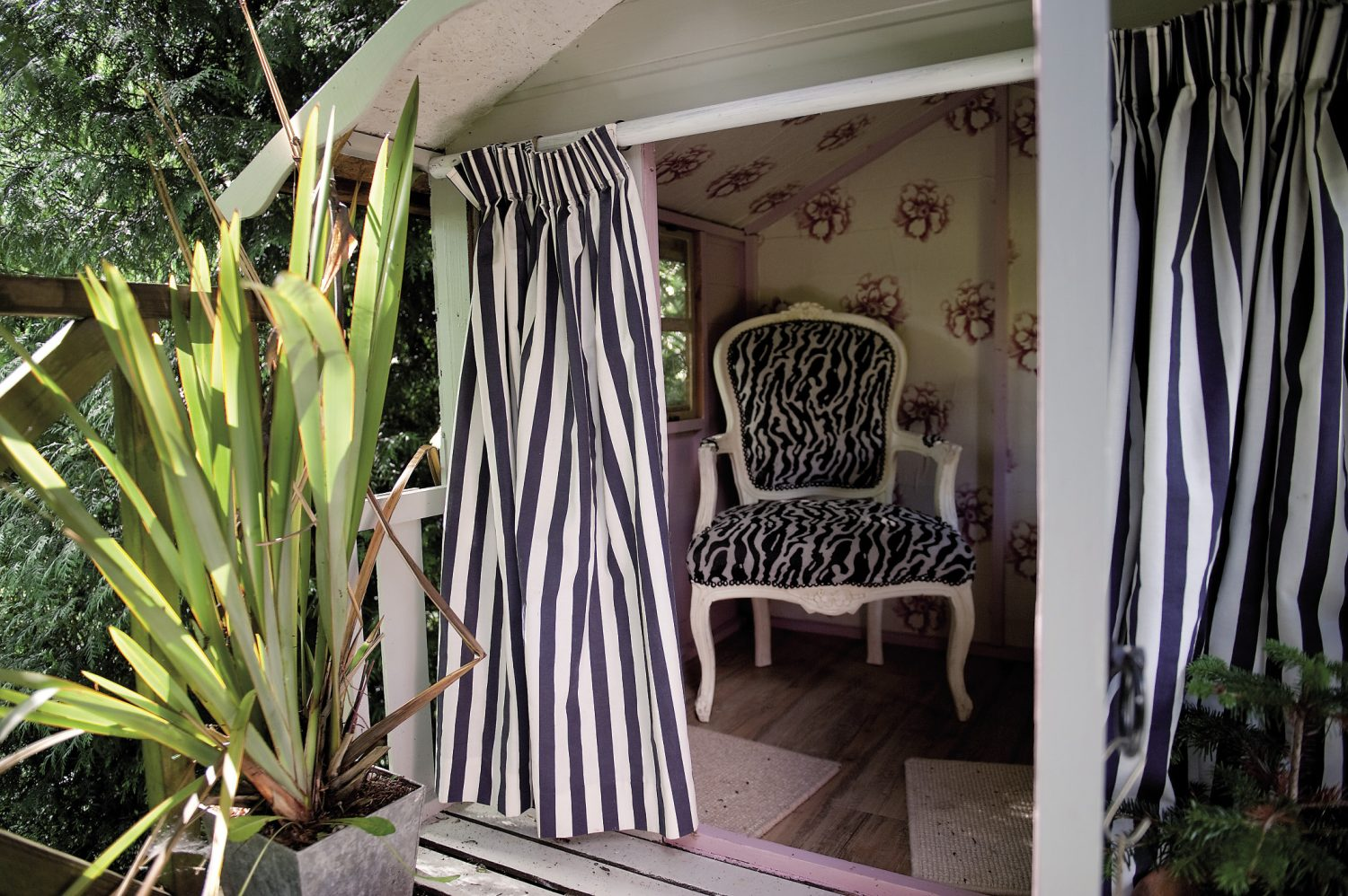 Down another set of steps and there, among the boughs of a fine oak tree is the treehouse, now painted white, with nautical blue and white striped curtains. Inside, Andrew has wallpapered it and added just one, throne-like chair